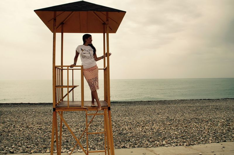 Full length of young woman standing in lifeguard hut at beach