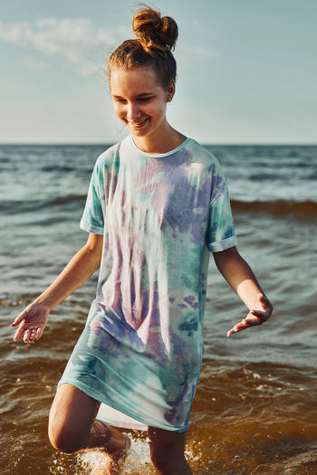 Girl spending a free time enjoying the sea and beach during summer vacation at sunset