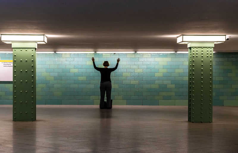 Station The Street Photographer - 2018 EyeEm Awards Underground Arms Raised Ceiling Electric Light Exercising Flooring Full Length Hands Up Healthy Lifestyle Human Arm Illuminated Indoors  Leisure Activity Lifestyles Light Light Fixture Lighting Equipment One Person Pillar Real People Rear View Standing Street Photography Tunnel Wall - Building Feature Women #urbanana: The Urban Playground This Is Strength