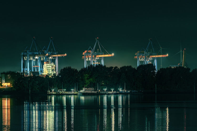Container Terminal Altenwerder Container Ship Trees Architecture Building Exterior Built Structure Commercial Dock Construction Equipment Container Bridges Container Terminal Crane - Construction Machinery Harbor Illuminated Industry Machinery Nature Night No People Outdoors Pier Pillars Reflection River Sky Water Waterfront Waterreflections