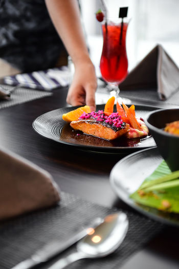 Midsection of woman holding plate with food on restaurant table