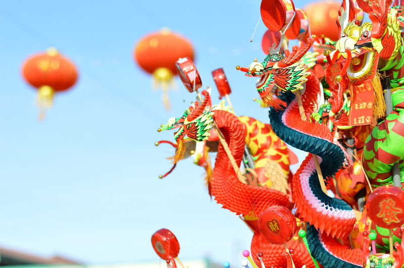 Close-Up Of Chinese Dragon Paper Doll At Store Against Clear Blue Sky