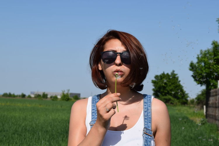 Young Woman Blowing Dandelion While Standing On Field During Sunny Day