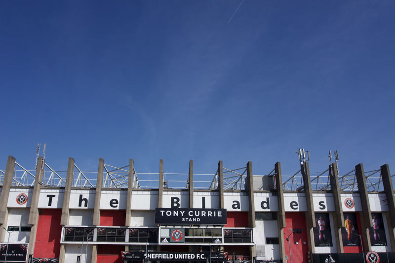 Exterior view of Tony Currie Stand at Bramall Lane Football Ground, Sheffield United.on a sunny day with blue sky and copy space Sheffield Sheffield United Bramall Lane Football Stadium Ground Standing Yorkshire Blades Clear Blue Sky Sunny Summer Sky Blue Text No People Day Copy Space Architecture Built Structure Building Exterior Clear Sky Low Angle View Western Script Sign Outdoors Building