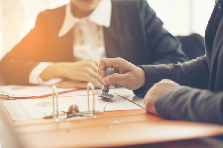Midsection Of Lawyers Working At Desk In Office