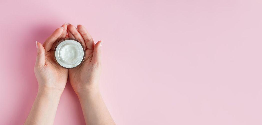 Close-up of woman hand holding pink over white background