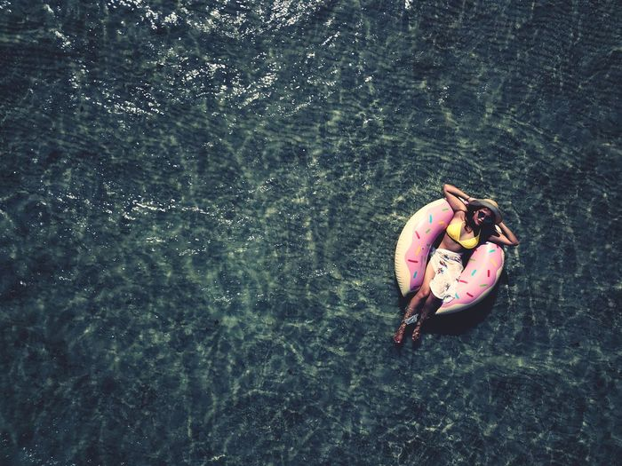 Directly above shot of woman on inflatable ring floating in sea