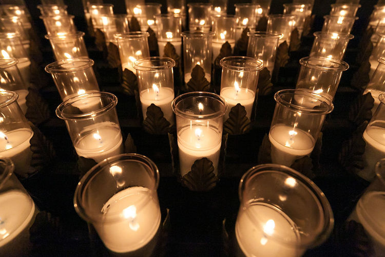 Full frame shot of lit tea light candles arranged in church