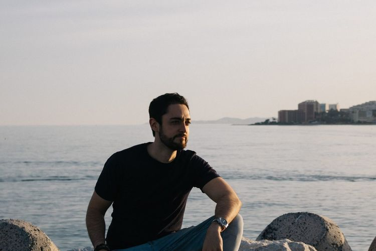Young man sitting on rock by sea against sky