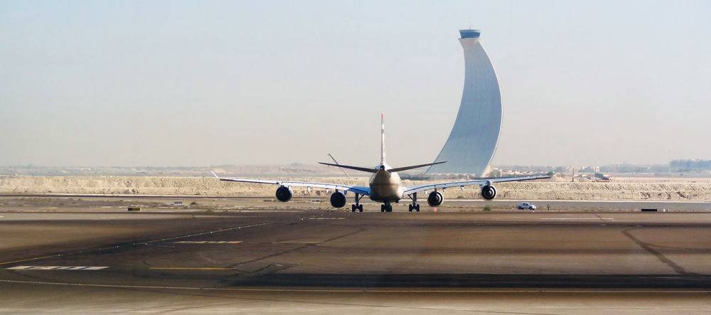 Aerospace Industry Air Vehicle Airfield Airplane Airport Airport Runway Commercial Airplane Day Landing - Touching Down Mode Of Transport No People Outdoors Passenger Boarding Bridge Sky Transportation Travel