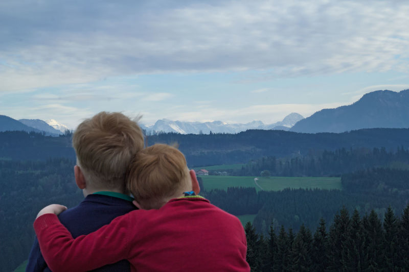 Rear view of siblings looking at mountains against sky