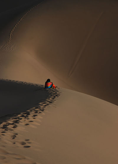 Rear View Of Woman Sitting On Desert During Sunset