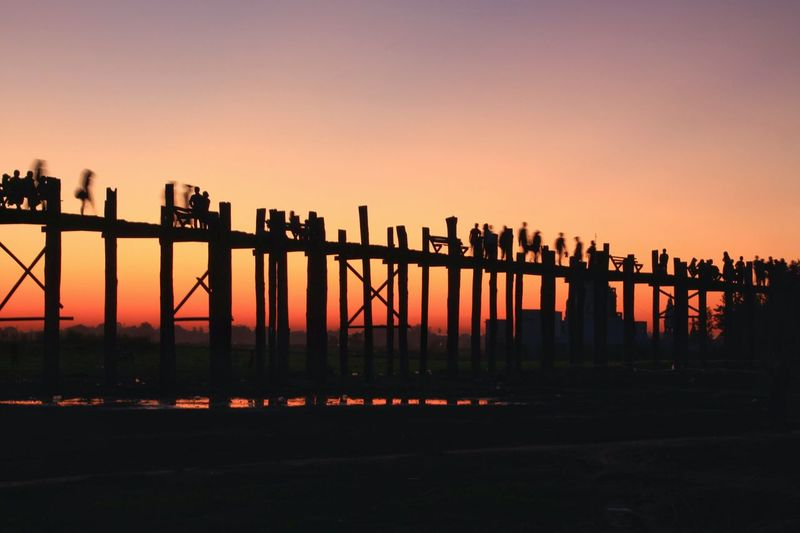 Silhouette of people traveling across the U Bein bridge in the evening, Mandalay Myanmar. People Travel Woodden Bridge Evening Sky Evening Light Mandalay Asianstyle Lifestyles Myanmar View Location Shoot สะพานอูเบ็ง Scenic View Shoot Places Scenery Dusk Dusk Sky Famous Places Pier Beauty In Nature Wonder Community Folk City Sunset Cityscape Urban Skyline Silhouette Sky Architecture