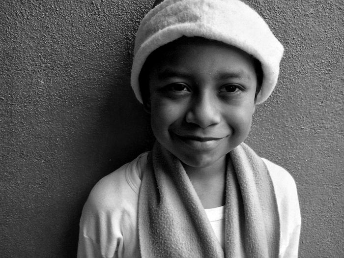 Close-up portrait of smiling boy standing against wall
