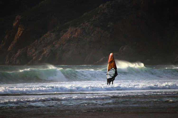 Person windsurfing in sea
