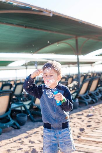 Boy blowing bubble at beach