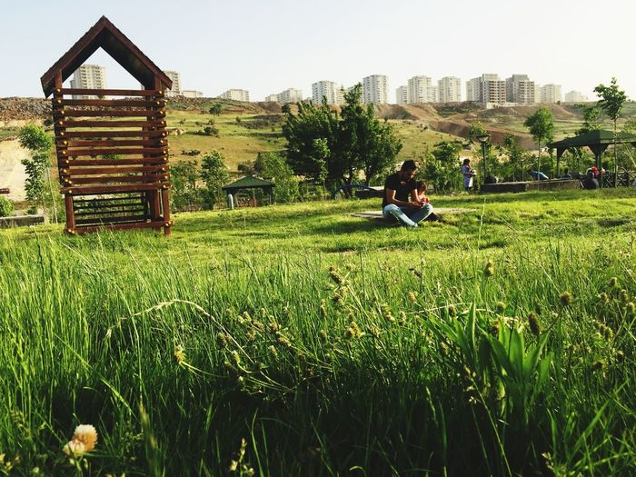 Growth Grass Field Real People Day Green Color Outdoors Building Exterior Nature Lifestyles Clear Sky Sky Beauty In Nature City Tree People Men EyeEmNewHere