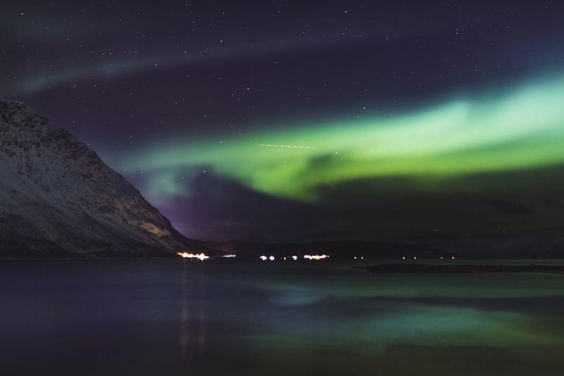 Scenic view of sea against sky  aurora borealis at night