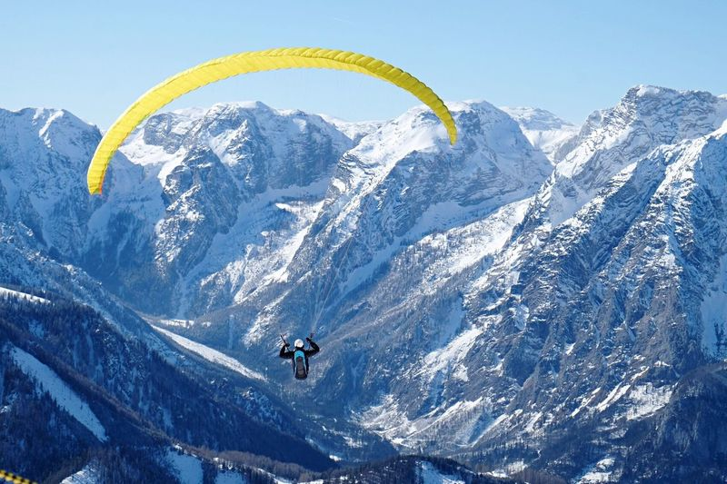 One Person Paragliding Against Snowcapped Mountain And Clear Sky