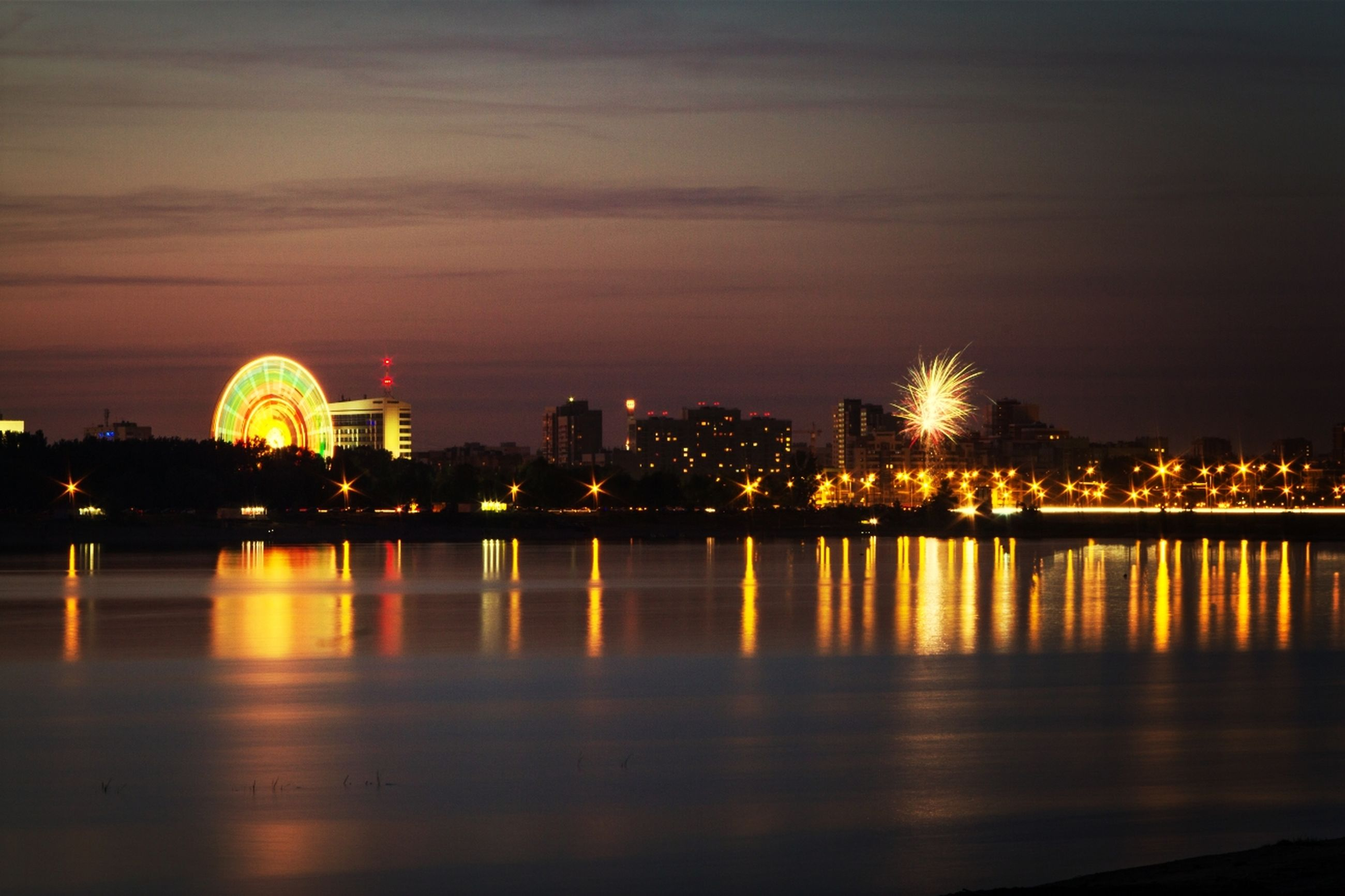 illuminated, reflection, water, night, waterfront, built structure, architecture, sky, city, building exterior, river, sunset, cityscape, long exposure, glowing, travel destinations, orange color, outdoors, city life, light