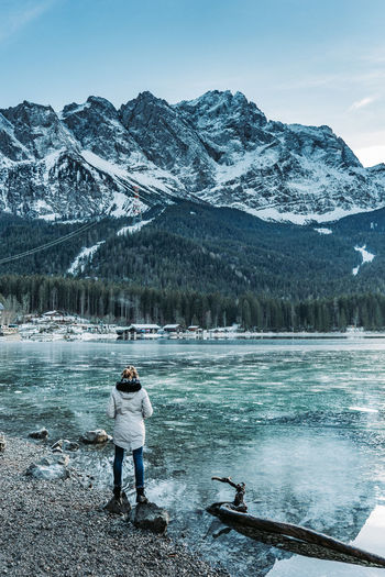Rear view of woman standing at lakeshore against snowcapped mountains