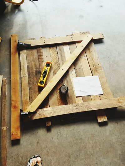High angle view of tools with paper on wood