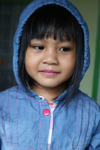 A portrait of an Asian girl wearing a hood was smiling Blue Casual Clothing Child Childhood Close-up Clothing Cute Focus On Foreground Front View Girls Happiness Headshot Hood - Clothing Innocence Looking At Camera One Person Portrait Real People Smiling
