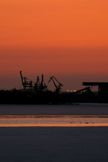Silhouette cranes on pier against sky during sunset