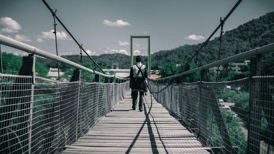 Rear view of man standing on footbridge against sky