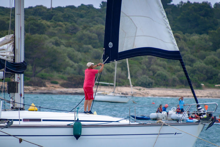 Rear view of man adjusting mast on sailboat in sea against trees