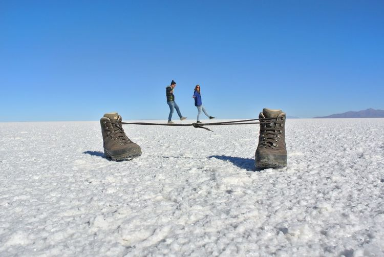 Salar de Uyuni. Nature_collection Travel Nature Uyuni Salt Flat Potosi Perspective Angle EyeEm Best Shots EyeEmNewHere Funny Pics Fun Couple Shoe Shoelace Uyuni Salar De Uyuni Sand Dune Full Length Clear Sky Blue Togetherness Cold Temperature Friendship Desert Winter Salt Lake Salt Flat Salt - Mineral Bolivia Arid Climate