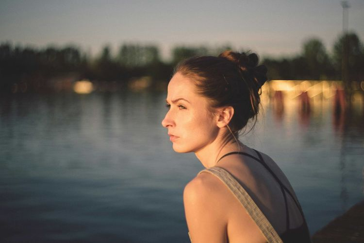 Portrait of young woman looking away while standing in lake during sunset