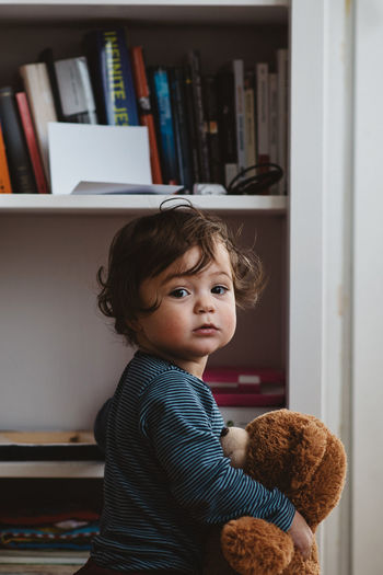 Portrait of baby girl holding teddy bear standing by shelf at home