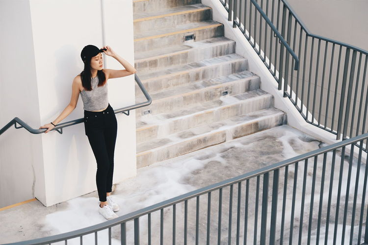 Full length of young woman standing by railing on staircase