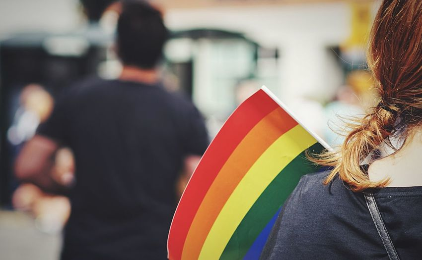 Rear view of woman with rainbow flag