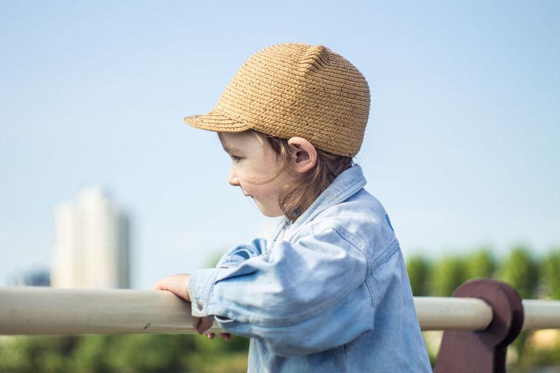 Cute Girl Looking Away By Railing Against Clear Sky
