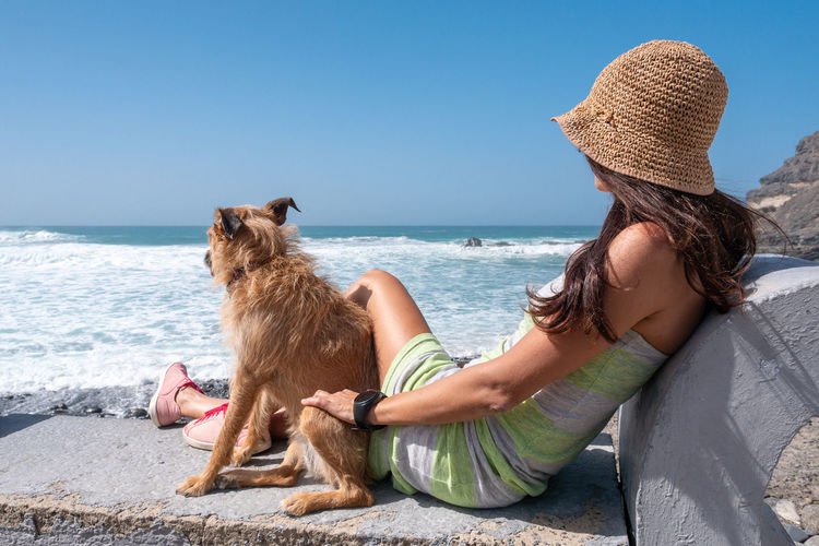 Mammal Sea One Animal Water Sky Domestic Domestic Animals Beach Pets Hat Sitting Land Nature Clothing Canine Women Dog Adult Hair Horizon Over Water Hairstyle Outdoors