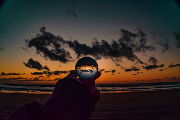 Man holding sunglasses at beach against sky during sunset