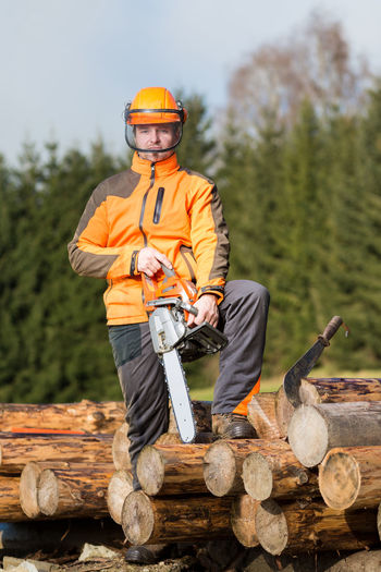 Portrait of man standing on logs