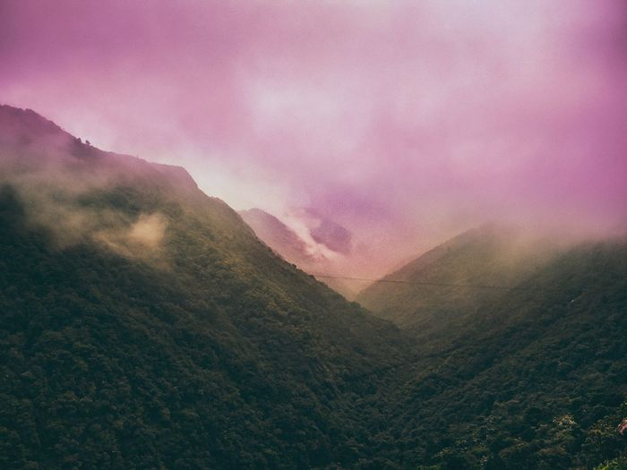 Scenic view of foggy mountains against sky during sunset