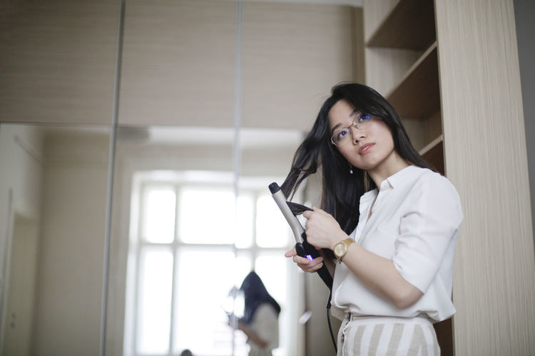 Low angle view of young woman curling hair at home