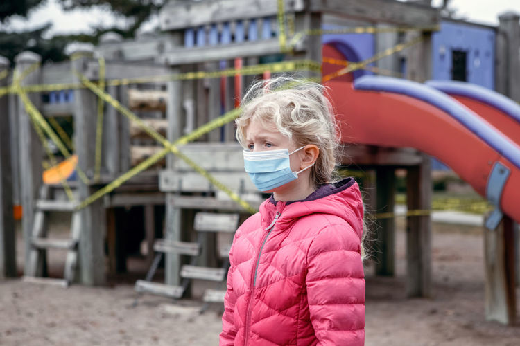 girl in face mask standing on closed playground. kids play area locked with yellow caution tape