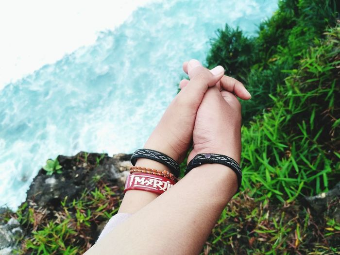 Cropped image of friends wearing bracelets holding hands against plants