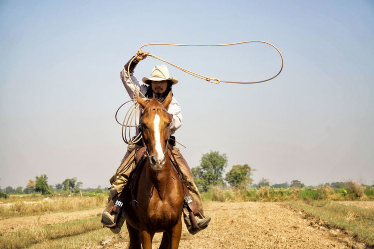 Portrait of cowboy holding rope while riding horse on land