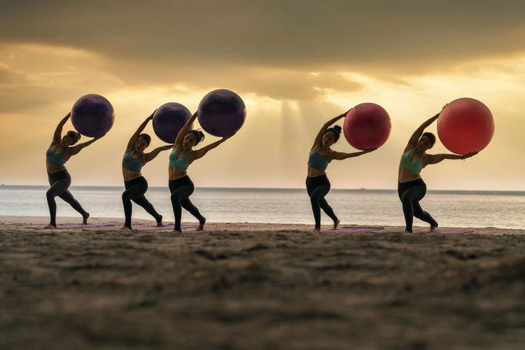 Women exercising at beach against sky during sunset