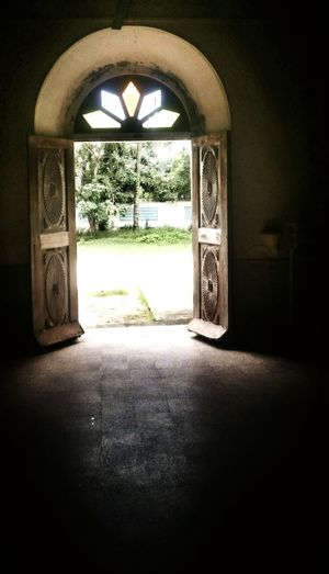 The Carved Open Doors of an Old Church provide Shade to those Inside , Framing the Kochi Green and Sunny Outside . Centuries Old Stained Glass crowns the Passage . Light And Shadow Urban Exploration Prayer Meditation Architecture Smartphone Photography Fine Art Photography Metaphor Composition Showcase July