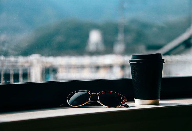 Close-Up Of Sunglasses And Coffee Cup