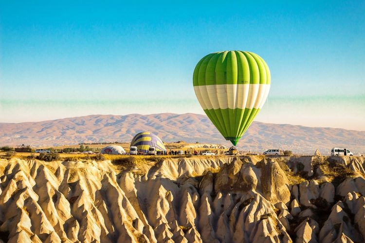 Hot air balloon flying at mountains against blue sky