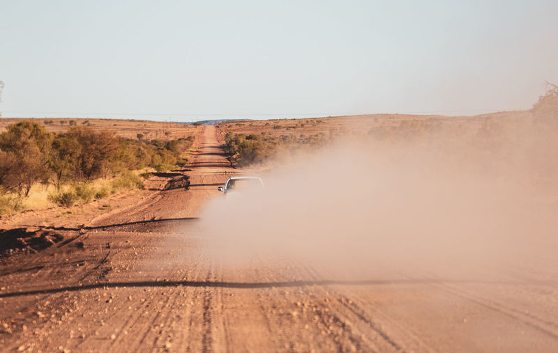 Car on dirt road amidst landscape against clear sky