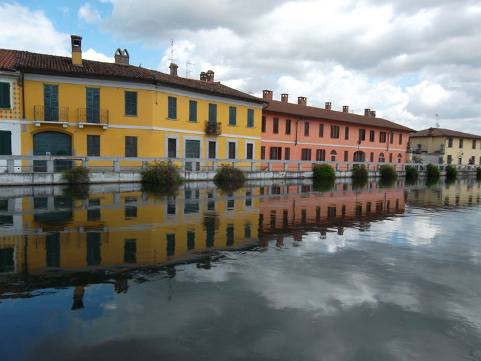 Walking around. Turistic Places Orange Color Yellow Color Eyeem Architecture Lover Teflection EyeEm Nature Lover Springtime Architecture Gaggiano Naviglio Grande EyeEm Selects City Cityscape Water Multi Colored Urban Skyline Riverbank Water's Edge Residential Structure Building Old Town Cloudscape Atmospheric Mood Cumulus Dramatic Sky Meteorology Cumulus Cloud